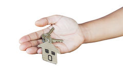 Holding house keys on house shaped keychain in front of a new ho Stock Photo