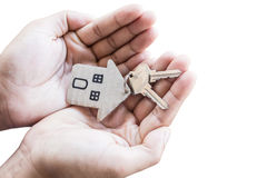 Holding house keys on house shaped keychain in front of a new ho Stock Photos