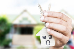 Holding house keys on house shaped keychain in front of a new ho Royalty Free Stock Image