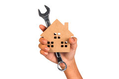 Holding house representing home ownership. Miniature house and wrench in hand. Holding house representing home ownership Stock Photography