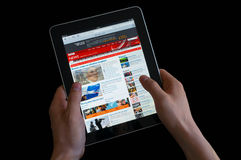 Holding an ipad while reading the BBC news. Photo of hands holding an ipad while reading the BBC news Royalty Free Stock Photos