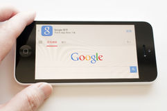 Holding iphone for google search engine Stock Photography