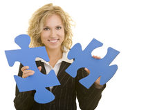 Holding jigsaw pieces. Blonde business woman holding two big jigsaw pieces stock photography
