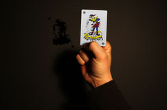 Holding joker card in hand Royalty Free Stock Images
