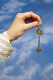 Holding a key. Hand holding a key over sky and clouds backgound Stock Photography