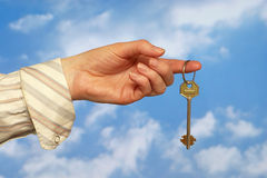 Holding a key. Hand holding a key over sky and clouds backgound Royalty Free Stock Photo
