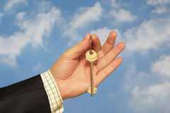 Holding a key. Hand holding a key over sky and clouds backgound Stock Photos