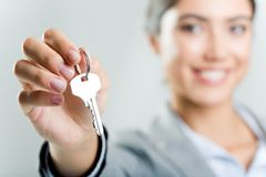 Holding key. Photo of happy woman�s hand holding new key and pointing it at camera Stock Photo