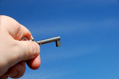 Holding key. Sky background stock photos