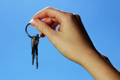 Holding keys. Hand holding keys with sky in background Stock Images