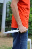 Holding a Knife. A close up view of someone wearing an orange shirt holding and griping a knife Royalty Free Stock Images
