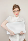 Holding laptop. Beautiful young girl with eyeglasses holding silver laptop in her hands royalty free stock image