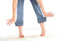 Holding lei stessa della ragazza per rotolato sui jeans. Fotografia Stock