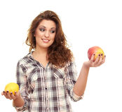 Holding a lemon and an apple. Beautiful girl isolated on white background holding a lemon and an apple Royalty Free Stock Photography