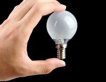 Holding light bulb with black background Royalty Free Stock Photography