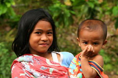 Holding little brother. Young indonesian girl holding her little brother Royalty Free Stock Images