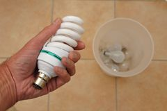 Holding a low energy CFL light bulb with discarded tungsten bulbs in background.  Stock Photo