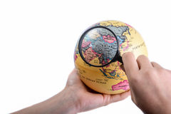 Holding a magnifying glass on globe. Hand holding a magnifying glass on globe in hand on white background Royalty Free Stock Photos