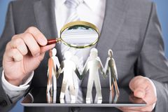 Holding magnifying glass and paper people Royalty Free Stock Photo