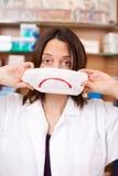 Holding Mask With för kvinnlig apotekare ledsen Smiley Royaltyfria Bilder