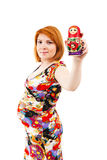 Holding Matrioska doll. Pregnant woman holding Matrioska doll. Pregnancy concept Royalty Free Stock Image