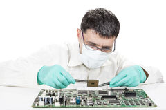 Holding Microchip. On electronic circuit board with tweezers on white background royalty free stock image