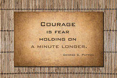 Holding on a minute longer - George S. Patton. Courage is fear holding on a minute longer. Quote by George S. Patton. Quote over stone and bamboo. Patton was one stock photo