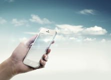 Holding a mobile. In a sky Royalty Free Stock Image