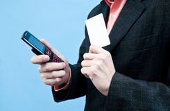 Holding mobile and white card. Business man holding mobile phone and white card Stock Image