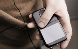 Holding MP3 player (close up). A hand holding a MP3 player. Screen can be used to hold text Royalty Free Stock Photography