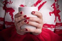Holding a mug. Closup of a Woman holding a hot coffee mug Stock Photos