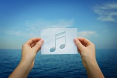 Holding music note. Woman hands holding a paper sheet with music note inside, over blue sea horizon background. Listening to the rhythm of ocean waves stock photos