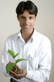 Holding a new life. Young man holding a new plant, environment concept Stock Photography