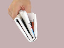 Holding the Newspaper. A newspaper, folded and held by a person stock images