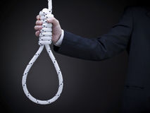 Holding the noose. A man on a suit holds a hangman's noose over a gray background Stock Images