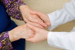 Holding old hands. The doctor holding an elderly woman's hand Stock Images