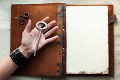 Holding an old key over a book.  Royalty Free Stock Image
