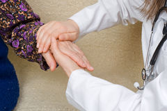 Holding old lady's hands. The doctor holding an elderly woman's hand Royalty Free Stock Images