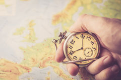 Holding old pocket watch in hand. With map of Europe behind Royalty Free Stock Photography