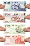 Holding onto my money. Hands holding out 100, 200, 500 and 1000 New Taiwan Dollar bills Royalty Free Stock Photos