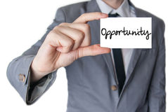 Holding an opportunity. Businessman holding or showing an opportunity on card Royalty Free Stock Images
