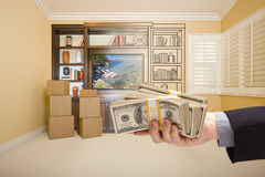 Holding Out Cash Over Drawing of Entertainment Unit In Room Stock Images