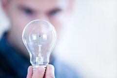 Holding out a lightbulb. Man holding lightbulb in front of out-of-focus face royalty free stock photos