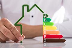 Holding outline of house model with energy efficiency rate royalty free stock photo
