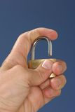 Holding a padlock. Hand holding an open padlock on blue background Royalty Free Stock Photo