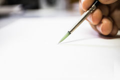 Holding paintbrush on white paper close up. Stock Image