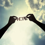 Holding paper cut of hope. Show the paper cut word in the sky Stock Images