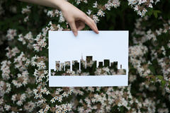 Holding paper cut miniature residential house over blooming Stock Photos