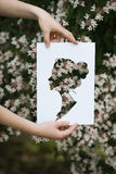 Holding paper cut miniature women portrait over blooming tree Royalty Free Stock Images