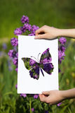 Holding papercut miniature butterfly over blooming flowers Stock Photography